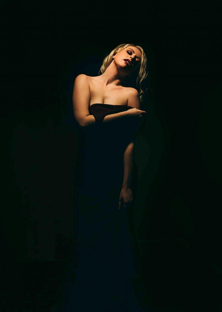 Gorgeous Woman Pulling Dress Over Shoulder During Edmonton Boudoir Photography Session
