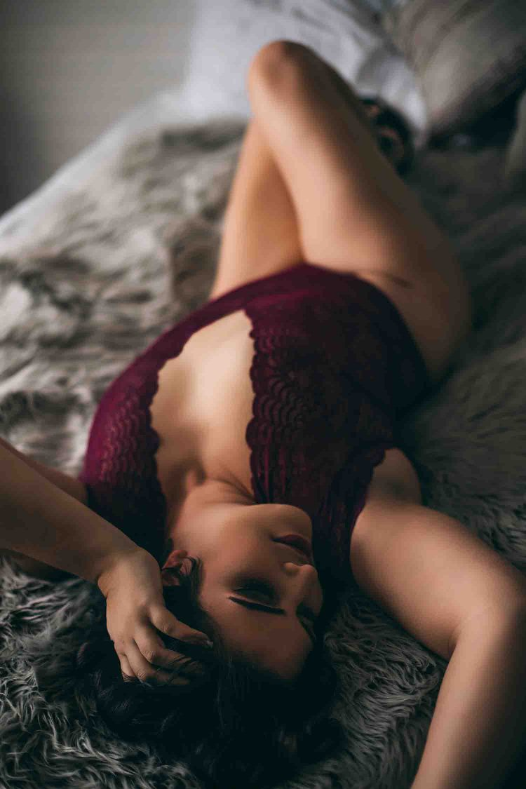 Relaxed Woman Laying Down on Grey Comforter during Edmonton Canada Boudoir Photography Session